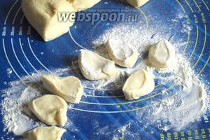 Разделить тесто на 3 одинаковые части, затем каждую часть поочерёдно скатать в колбаску и нарезать кусочками. Обвалять кусочки в муке.