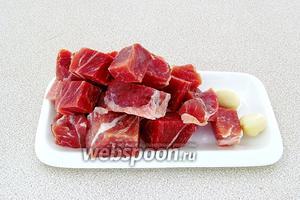 Мясо нарезать кусочками, дольки чеснока очистить от сухой оболочки.