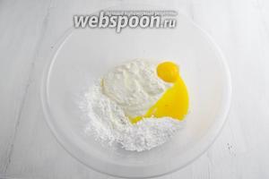 Мягкий творог (если нужно, протереть через сито), сахарную пудру, кукурузный крахмал, 2 желтка, ванильную эссенцию поместить в глубокую миску.