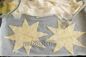 Отрываем излишки от звёзд, убираем в сторону, растопленным маслом (2 ст. л.) смазываем звёзды и протыкаем дырочки вилкой.