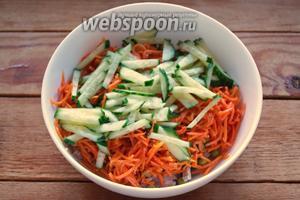 Свежий огурец нарезать соломкой и добавить в салатник.