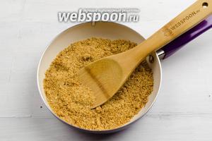 Разогреть 1 ст. л. топлёного масла на сковороде, всыпать панировочные сухари. Перемешивая, жарить до румяности.