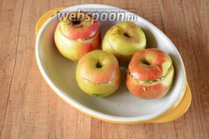 Немного в форму добавить воды (100 мл), накрыть яблоки верхним срезом.