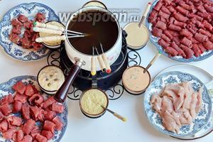Сервируем. Кастрюля с бульоном на горящем огнём рехауде, соусы и мясо. На вилку нанизывается мясо и варится в бульоне 1 минуту или 2, говядина и оленина меньше 1 минуты. Мясо снимается с вилки в тарелку и обмакивается в один из соусов. Приятного аппетита!