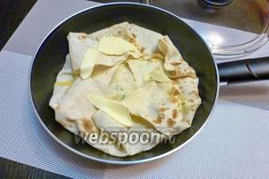 Выльем в лаваш яично-молочную смесь и сверху прикроем свисающими краями лаваша. Сверху выложим опять несколько кусочков сливочного масла.