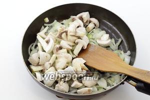 Лук нарежьте произвольными кусочками, можно полукольцами. Шампиньоны промойте. По желанию, удалите кожицу. Разрежьте на 4 части вместе с ножками. На подсолнечном масле обжарьте лук до мягкости. Добавьте грибы. Перемешайте и обжарьте до готовности.