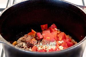Затем черёд сладкого перца, острого перца и чеснока. Многие хозяйки чеснок добавляют в конце варки, а я люблю добавлять при обжаривании. Помешивая, жарить овощи с мясом 5 минут. Если начнёт быстро пригорать, то можно влить чуток воды — совсем немного.
