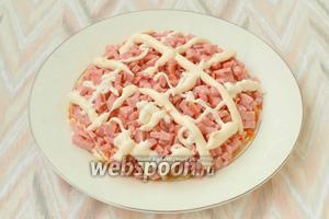 Колбасу нарезать кубиками, выложить сверху моркови и смазать майонезом.