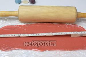 Торт выносим в холод. Раскатываем между 2-мя пищевыми плёнками розовый марципан, по весу около 260-270 г в пласт, около 3 мм.