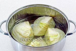 Четвертинки кочана сложить в кастрюлю, залить горячей подсоленной водой и отварить до полуготовности, а затем отжать.