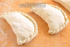 Слепите из каждой заготовки пирожок в виде полумесяца и оформите края как у «писанных» вареников.