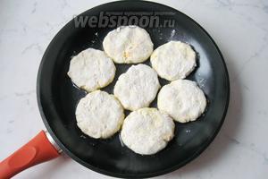 Из теста сформировать круглые лепёшки и обвалять их в муке. Выложить на горячую сковороду с подсолнечным маслом.