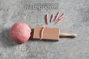 Колбаска, сразу после того, как её скатали, прокатывается вдоль рифлёной поверхности так, чтобы на ней отпечатались полоски.