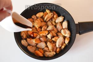 Добавляем соевый соус и, помешивая, ждём, когда мидии вберут его в себя.