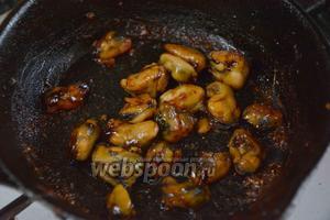 На разогретую сковороду с подсолнечным маслом, выкладываем мидии и обжариваем в течении 2-3 минут.