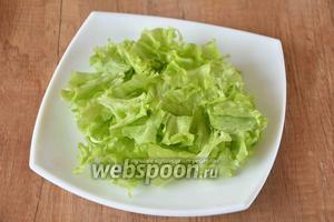 Пока мидии обжариваются, на тарелку выкладываем порванные руками листья салата.