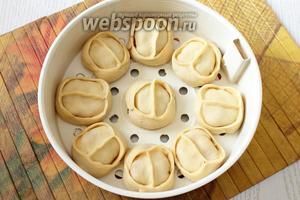 Форму для варки на пару (для мультиварки) или решётку (для мантышницы) смазываем сливочным маслом, укладываем манты.