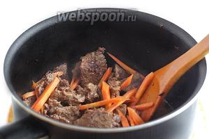 Обжарить мясо на растительном масле до изменения цвета и легкого румянца. Затем слегка посолить, добавить морковь. Жарить пару минут.