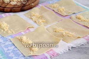 Мокрые заготовки разложить на полотенце, с одного края посыпать сырной стружкой.