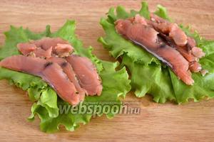 Положите сверху листья салата и ломтики красной рыбы.