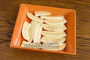 Бананы почистите, нарежьте вдоль на половинки, возможно что и поперёк нужно нарезать, чтобы поместились в форму. Обильно брызните лимонным соком. Поместите их в форму для запекания, смазанную сливочным маслом.
