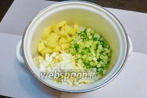 В подготовленную кастрюлю нарежем мелким кубиком картофель, огурец и яйца.