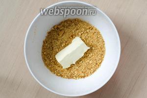 Печенье измельчаем в мелкую крошку и смешиваем с размягчённым сливочным маслом до однородности.