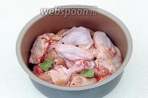Выложить куски курицы в чашу мультиварки, посыпая солью, крупно разломанным лавровым листом и горошинами перца. Воды и масла в чашу не добавлять!