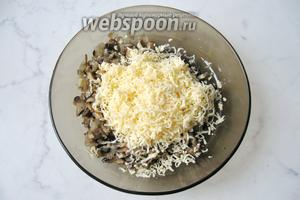К жареным шампиньонам и луку добавить тёртый сыр.