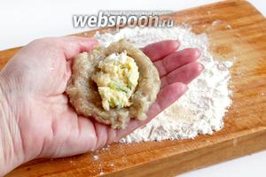 Влажными руками сформировать лепёшку из фарша, в центр положить немного начинки и слепить котлету.