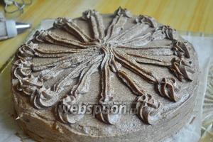 Последний корж и бока смазать кремом. Оставшийся крем отправить в кондитерский мешок и от центра к краю торта сделать длинные полоски, а на конце кружок. Полосок должно быть столько, сколько у вас карамельных кусочков.