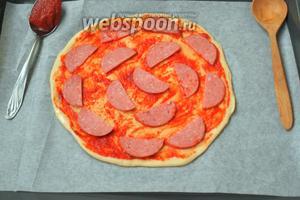 Разложить на тесте колбасу, стараясь равномерно выкладывать кусочки.