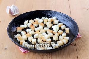 На раскаленной сковороде прогреть оливковое масло, бросить раздавленный зубок чеснока и до золотистого цвета подсушить хлеб.
