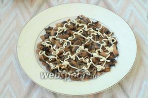 Обжаренные грибы с луком выложить на тарелку в форме круга, нанести сверху майонезную сеточку.