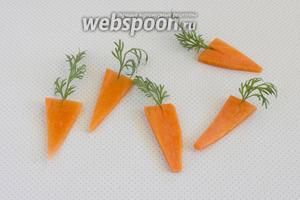 Морковь нарежьте пластинками, толщиной примерно 2 мм. Вырежьте треугольнички. Сделайте в каждом надрез и вставьте по веточке укропа.