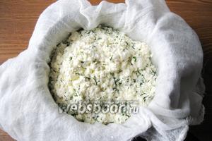 Дуршлаг или сито поставить на кастрюлю и выстелить марлей в 2-3 слоя. Вылить содержимое кастрюли и дать стечь сыворотке. Затем накрыть сыр марлей, поставить сверху блюдце, а на блюдце груз. Отправить сыр в холод на 6-7 часов. Можно на ночь.