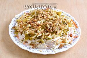 Яблоки и огурцы нарежьте острым ножом на тонкие ломтики. Выложите поверх соуса, посыпьте нарубленными орехами.