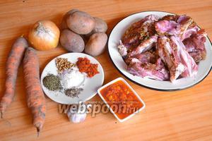 Подготовьте необходимые ингредиенты для приготовления шурпы: морковь, картофель, лук, мясо, чеснок, аджику и специи.