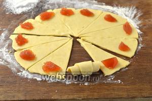 Дальше переложить тесто в холодильник. По 1 куску брать тесто и раскатывать в круг толщиной 3-4 мм. Разрезать его на 12 частей. На  широкий край каждой  части выложить 1 чайную ложку любой начинки: джема, шоколада, смеси изюма и орехов. Свернуть рогалики.