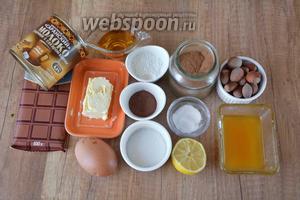 Для приготовления необходимы яйца, сахар, масло сливочное, шоколад, мёд, какао, мука пшеничная, корица, разрыхлитель, ванилин, лимон, коньяк, варёная сгущёнка, орехи фундук.