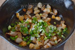 Зелёный лук мелко порезать, добавить в сковороду. Перемешать и обжарить на среднем огне ещё 2-3 минуты.