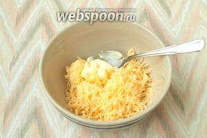 Натереть твёрдый сыр на мелкой тёрке, выдавить зубок чеснока, добавить майонез и перемешать.