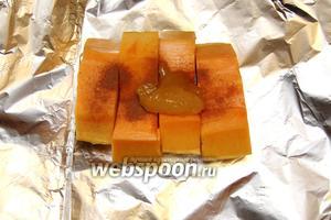 Выкладываем на фольгу тыкву, посыпаем корицей и кладём мёд.