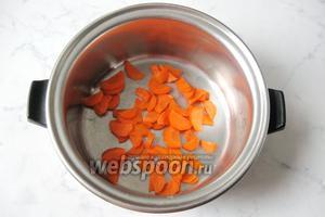 Приготовить томатный соус. Морковь почистить, помыть и нарезать. Выложить в кастрюлю.