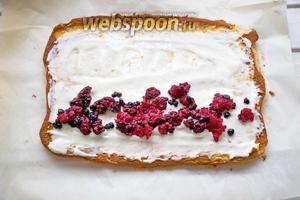 На бисквит нанесите взбитые сливки и вдоль длинной стороны выложите 60 г предварительно размороженных ягод (либо свежих). Сверните рулетом.