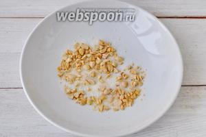 Орешки порежем ножом и смешаем с сахаром в широкой посуде.
