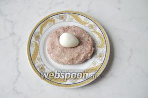 Из порции фарша сформировать лепёшку. На середину лепёшки выложить яйцо.