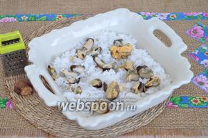 Форму для запекания смажем маслом (10 мл) и выложим слой риса. Затем выложим мидии и добавим немного мускатного ореха (1 г). Можете добавить соль по вкусу, я соль не добавляю.