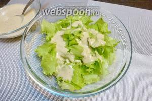 Листья салата (штуки 3) крупно рвём, кладём в миску и заливаем соусом, тщательно перемешаем, чтобы все листья обволокло соусом.