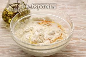 К просеянной муке вливаем яичную смесь, опару, 30 мл растительного масла.
